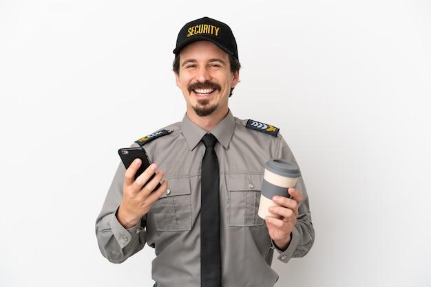 Молодой человек безопасности кавказской изолирован на белом фоне, держа кофе на вынос и мобильный