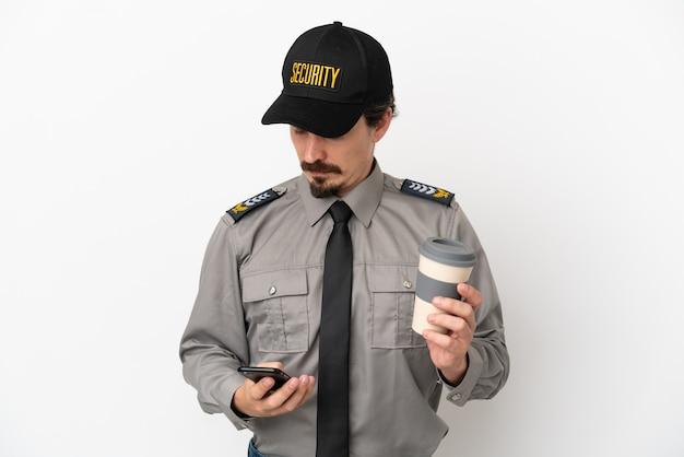 持ち帰り用のコーヒーと携帯電話を保持している白い背景で隔離の若い白人警備員