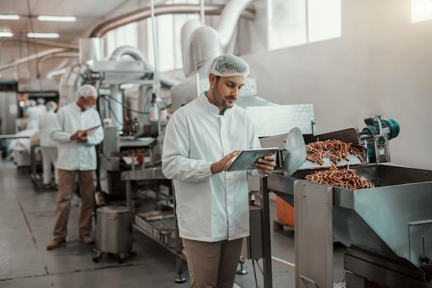 Молодой кавказский серьезный руководитель, оценивающий качество еды на пищевом заводе, держа таблетку. мужчина одет в белую форму и с сеткой для волос.