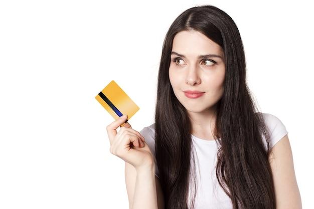 Молодая кавказская сексуальная брюнетка в белой футболке демонстрирует свою золотую кредитную карту для макета