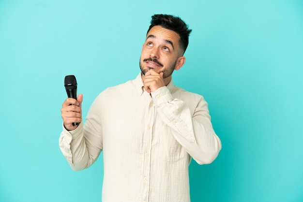 Молодой кавказский певец мужчина изолирован на синем фоне и смотрит вверх