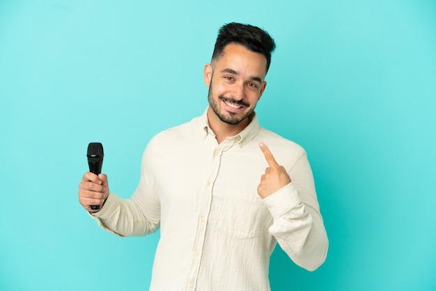 Молодой кавказский певец мужчина изолирован на синем фоне, показывая большой палец вверх жест