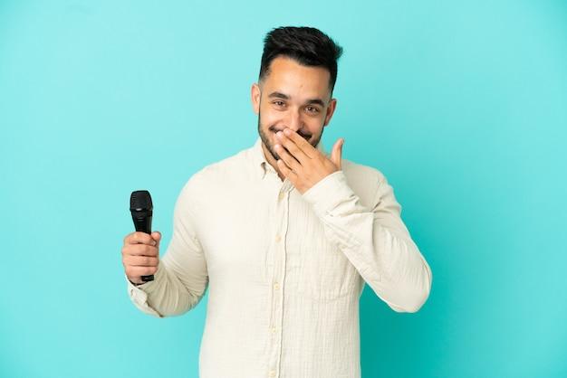Молодой кавказский певец мужчина изолирован на синем фоне, счастливый и улыбающийся, прикрывая рот рукой