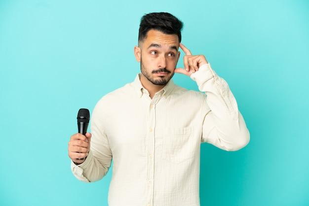 Молодой кавказский певец мужчина изолирован на синем фоне, сомневаясь и думая