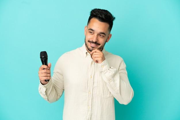 Молодой кавказский певец мужчина изолирован на синем фоне, глядя в сторону и улыбается