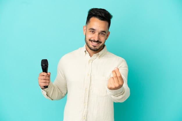 Молодой кавказский певец мужчина изолирован на синем фоне, делая денежный жест