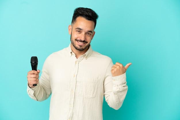 Молодой кавказский певец мужчина изолирован на синем фоне, указывая в сторону, чтобы представить продукт