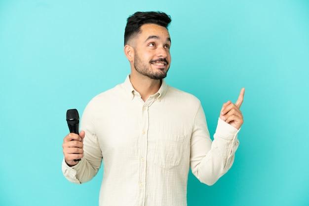 Молодой кавказский певец мужчина изолирован на синем фоне, указывая на отличную идею