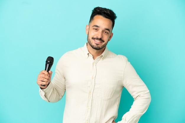 Молодой кавказский певец мужчина изолирован на синем фоне позирует с руками на бедрах и улыбается