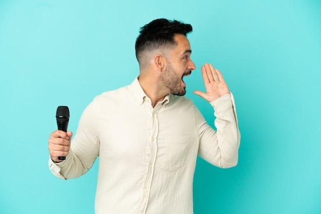 Молодой кавказский певец, изолированный на синем фоне, кричит с широко открытым ртом в сторону