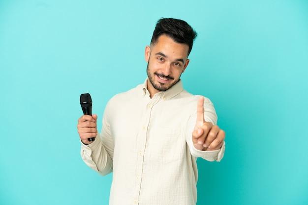 Молодой кавказский певец мужчина изолирован на синем фоне, показывая и поднимая палец