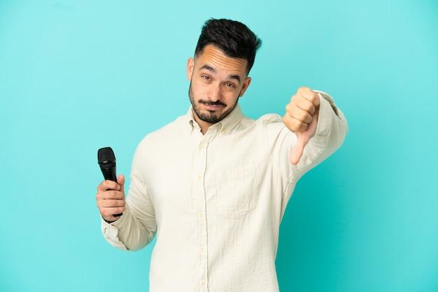 Молодой кавказский певец мужчина изолирован на синем фоне, показывая большой палец вниз с отрицательным выражением лица