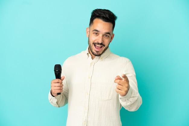Молодой кавказский певец мужчина изолирован на синем фоне удивлен и указывает фронт