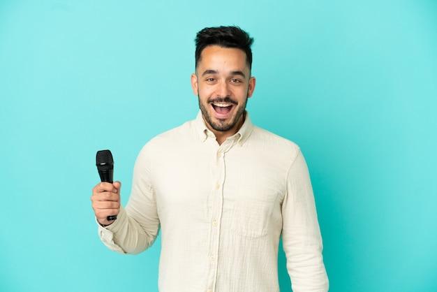 Молодой кавказский певец мужчина изолирован на синем фоне с удивленным выражением лица
