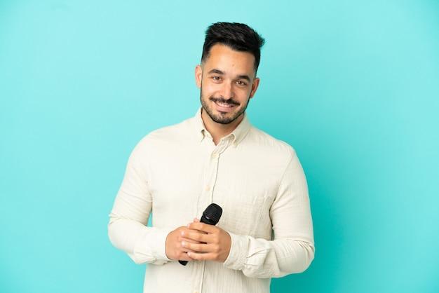 Молодой кавказский певец мужчина изолирован на синем фоне