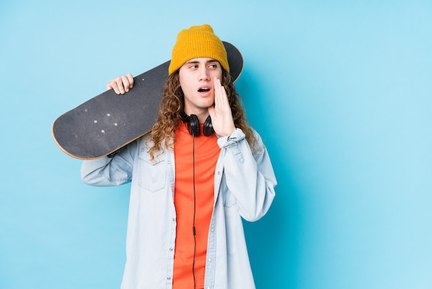 Young caucasian skater man isolated is saying a secret hot braking news and looking aside