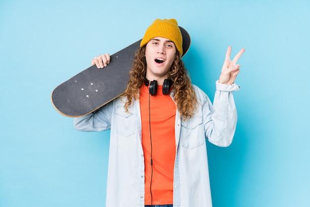 젊은 백인 스케이팅 남자는 손가락으로 평화의 상징을 보여주는 즐겁고 평온한 고립.