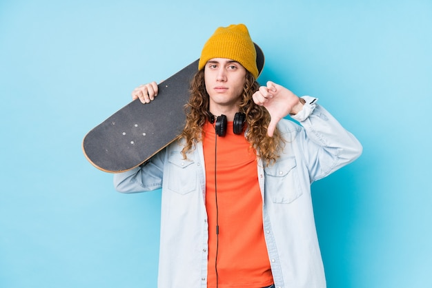Young caucasian skater man showing a dislike gesture, thumbs down. disagreement concept.