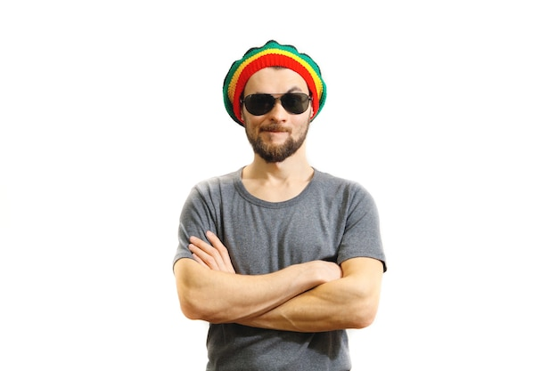 Young caucasian skeptic man in rasta hat, sunglasses and grey t-shirt on white background.