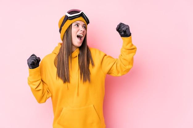 若い白人スキーヤー女性は勝利、勝者の概念の後、拳を上げて分離しました。