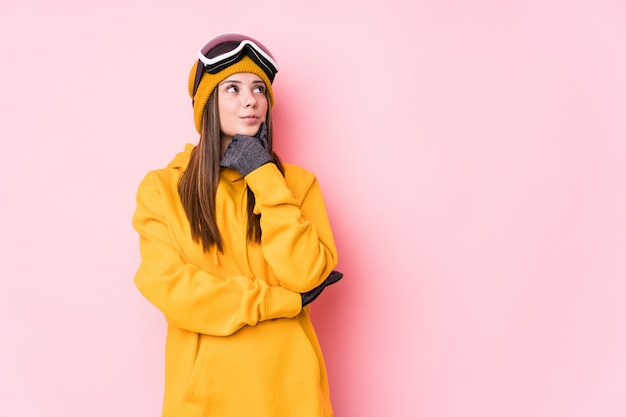 Young caucasian skier woman looking sideways with doubtful and skeptical expression.
