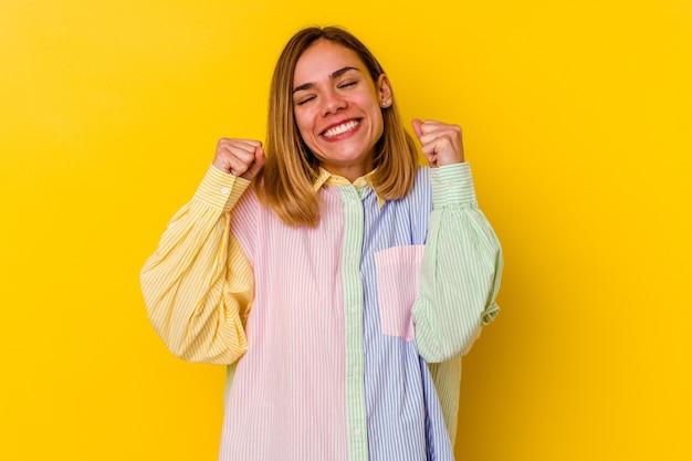 勝利、情熱と熱意、幸せな表現を祝う黄色の背景に分離された若い白人スキニー女性。