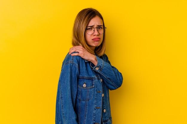 Молодая кавказская тощая женщина изолирована на желтом фоне с болью в плече.