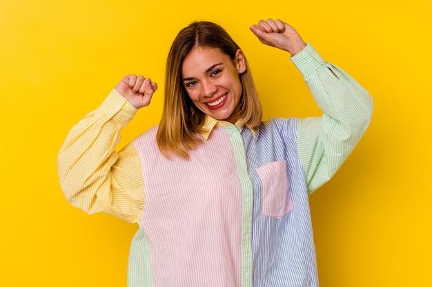 Молодая кавказская тощая женщина, изолированная на желтом, празднует особый день, прыгает и поднимает руки с энергией.