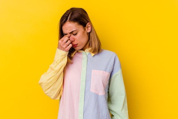 Молодая кавказская тощая женщина, изолированная на желтом, с головной болью, касаясь передней части лица.
