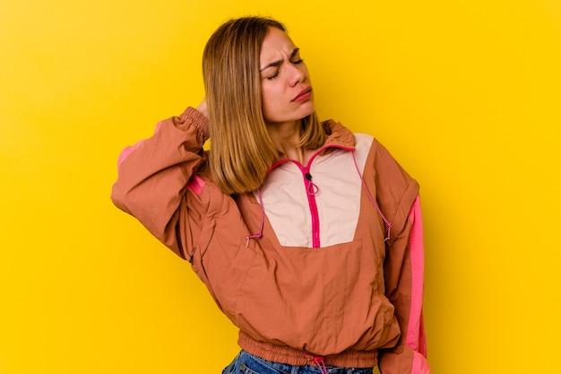 ストレス、マッサージ、手で首の痛みのために首の痛みを持っている黄色で隔離された若い白人の細い女性。