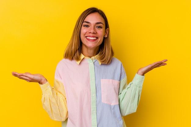 Молодая кавказская тощая женщина, изолированная на желтом, делает масштаб с руками, чувствует себя счастливой и уверенной.