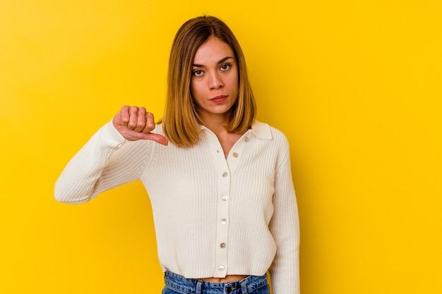 Молодая кавказская тощая женщина изолирована на желтом, показывая жест неприязни, пальцы вниз. концепция несогласия.