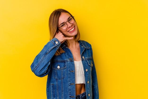 손가락으로 휴대 전화 제스처를 보여주는 노란색에 고립 된 젊은 백인 마른 여자.