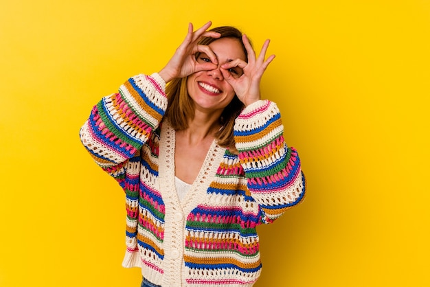 눈 위에 괜찮아 기호를 보여주는 노란색에 고립 된 젊은 백인 마른 여자
