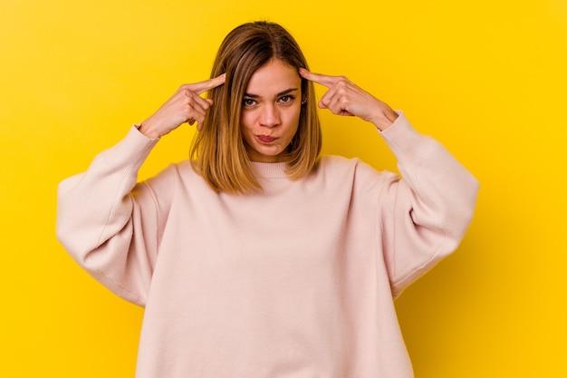 노란색 벽에 고립 된 젊은 백인 마른 여자는 머리를 가리키는 집게 손가락을 유지하는 작업에 초점을 맞춘.