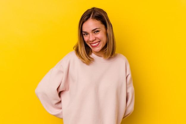 黄色の壁に隔離された若い白人の細い女性は幸せで、笑顔で陽気です。