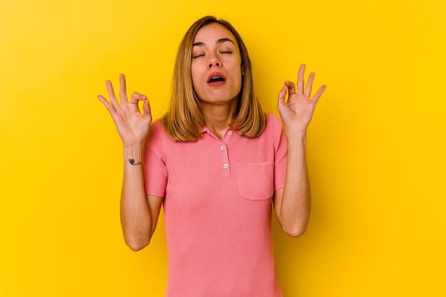 노란색 벽에 고립 된 젊은 백인 마른 여자는 열심히 일한 후 이완, 그녀는 요가를 수행하고 있습니다.