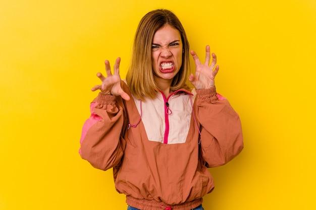 猫を模倣した爪、攻撃的なジェスチャーを示す黄色の壁に分離された若い白人スキニー女性