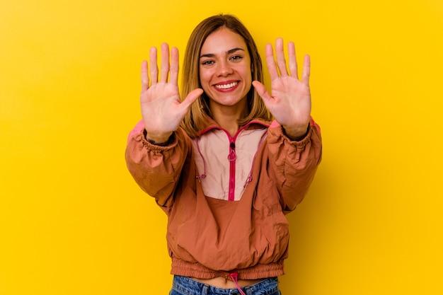 黄色の壁に孤立した若い白人の細い女性は、手で10番を示しています。