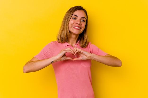笑顔と手でハートの形を示す黄色の壁に分離された若い白人スキニー女性。