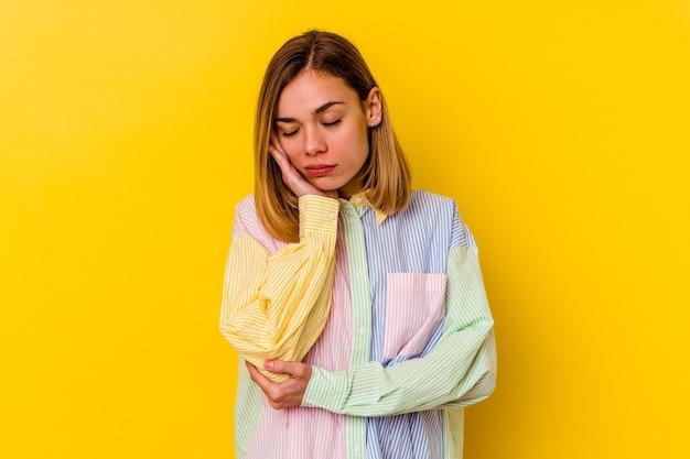 Молодая кавказская тощая женщина изолирована на желтом, которой скучно, устало и ей нужен день отдыха.