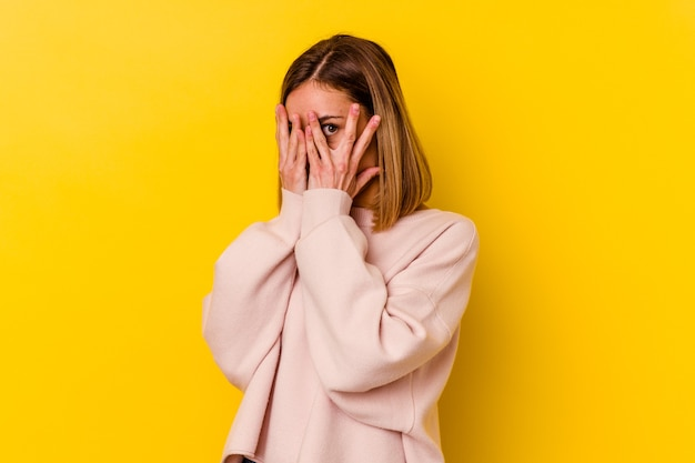 Young caucasian skinny woman isolated on yellow wall blink through fingers frightened and nervous.