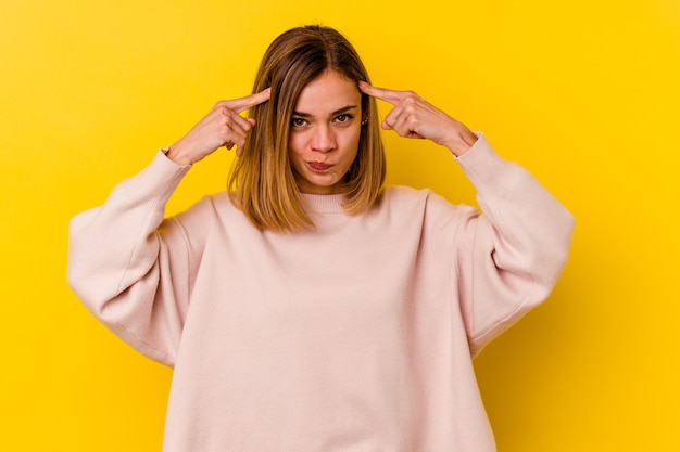 Young caucasian skinny woman isolated on yellow wall focused on a task, keeping forefingers pointing head.