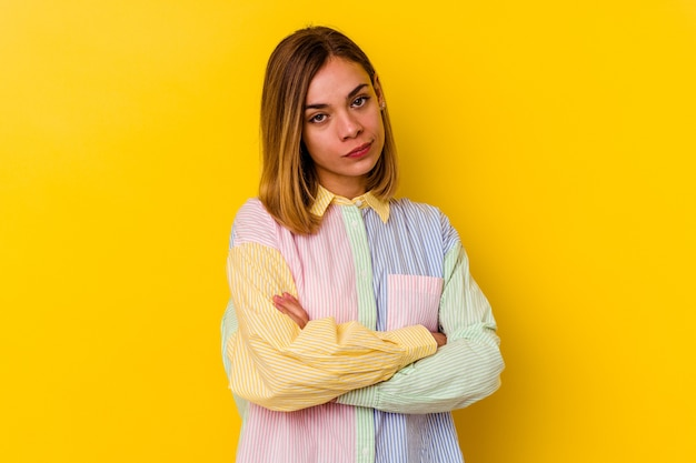 Young caucasian skinny woman isolated on yellow wall suspicious, uncertain, examining you.
