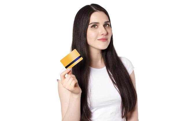 Молодая кавказская улыбающаяся брюнетка в белой футболке держит кредитную карту золотого банка для макета
