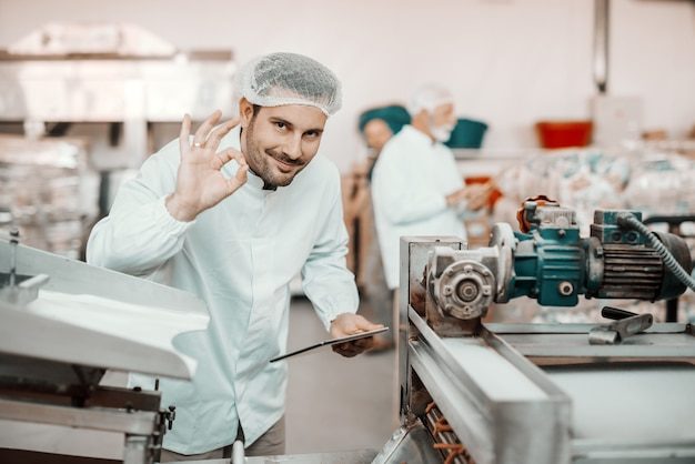 Young caucasian smiling supervisor evaluating quality of food in food plant while holding tablet and showing okay sign. man is dressed in white uniform and having hair net.