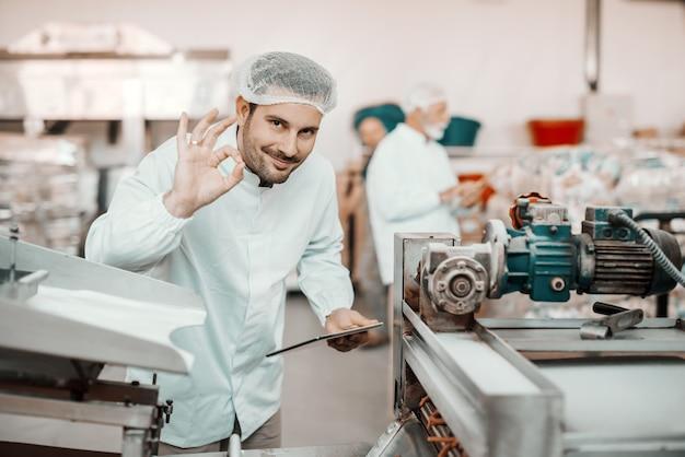 Молодой кавказский улыбающийся руководитель, оценивающий качество продуктов питания на пищевом заводе, держа в руках таблетку и показывая хорошо знаком. мужчина одет в белую форму и с сеткой для волос.