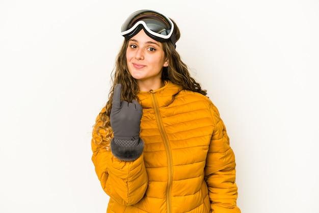 Молодая кавказская женщина сноубордиста изолировала указывая пальцем на вас, как будто приглашая подойти ближе.