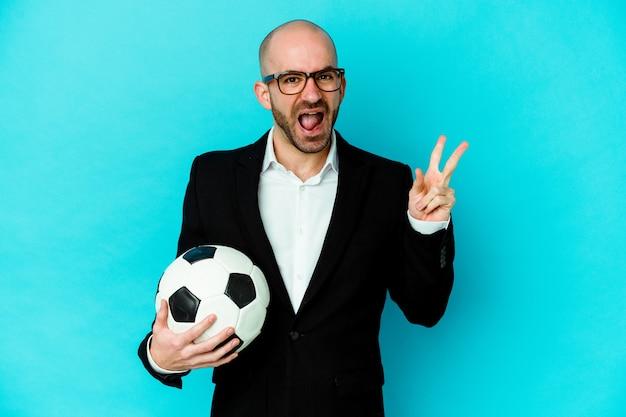 指で平和のシンボルを示す楽しくてのんきな白い壁に隔離された若い白人サッカートレーナー。