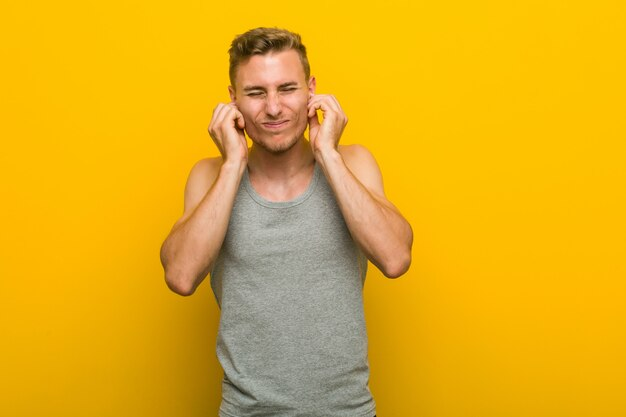 Young caucasian sport man covering ears with hands.